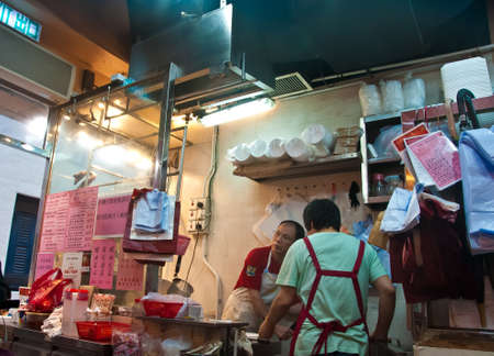 HONG KONG, HONG KONG SAR - NOVEMBER 17, 2018: Chef and waitress busily cook famous roasted goose and BBQ pork on rice for customer in Yat Lok Michelin stars restaurant in central Hong Kong. 報道画像