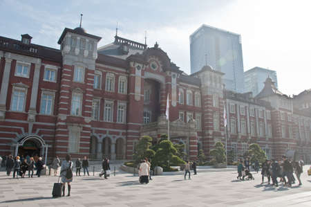 TOKYO, JAPAN - DECEMBER 1, 2018:  Tokyo Station railway building with warm sunlight shines to trees in late Autumn. There are many people walk on the street in front of the station.