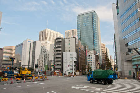 TOKYO, JAPAN - DECEMBER 1, 2018:  Japanese pedestrain stands to wait for traffic light before crossing the road near construction site in the morning.