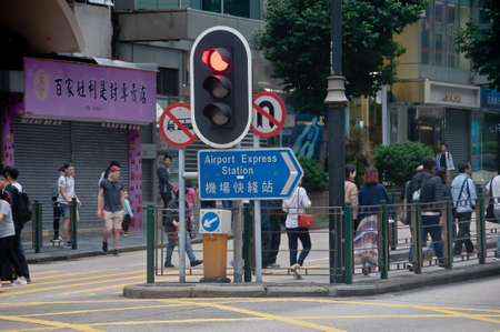 HONG KONG, HONG KONG SAR - NOVEMBER 18, 2018: Red person STOP traffic light in the city center above a sign to Airport Express station. There are many people in the photo. 報道画像
