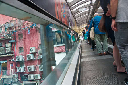 HONG KONG, HONG KONG SAR - NOVEMBER 17, 2018: Hong Kong famous Central-Mid-Levels escalator and walkway with many people stands in the photo. This escalator is the under the roof longest escalator system in the world.