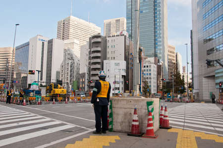 TOKYO, JAPAN - DECEMBER 1, 2018:  Japanese construction workers stand to wait for traffic light before crossing the road near construction site in the morning. 報道画像