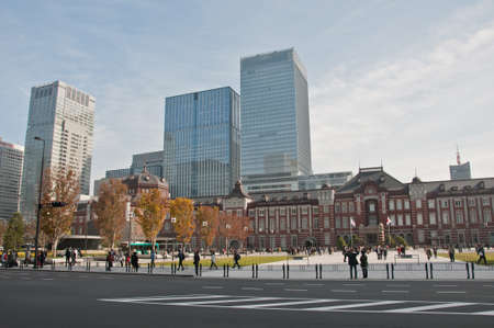 TOKYO, JAPAN - DECEMBER 1, 2018:  Tokyo Station railway building with Gingko yellow foliage leaves trees in late Autumn. There are many people walk on the street in front of the station.