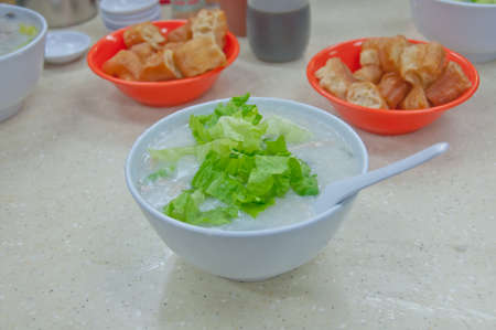 Fresh plain congee rice porrridge topping with green shallot and Chinese donut in Hong Kong