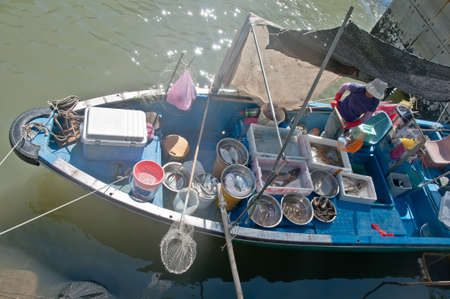 HONG KONG, HONG KONG SAR - NOVEMBER 18, 2018: Hong Kong Tai O local fisherman village in the Sunny afternoon. Female fisher is in her boat to sale fresh seafood.