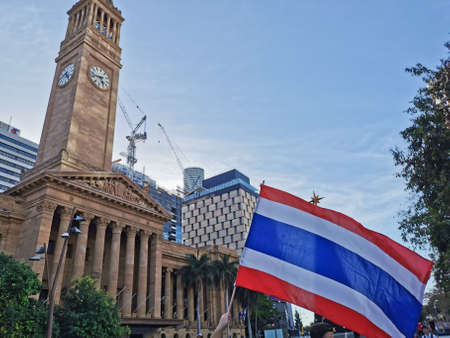 BRISBANE, AUSTRALIA - NOVEMBER 29, 2020: Protestor holds Thailand national flag in the peacefully rally at King George Square, City Hall, in Brisbane Australia to protest the dictatorship of the prime minister Prayuth Chan-ocha in Thailand and also protes