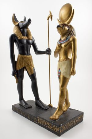 ankh: Statues of Anubis and Horus in human form standing at 90 degrees to each other on a white background.