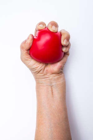 Senior womans hand squeezing red stress ball on white background