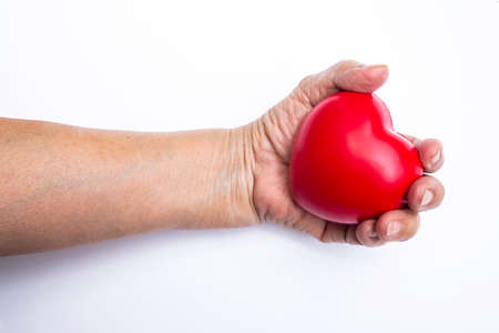 Senior womans hand holding red stress ball on white background 写真素材