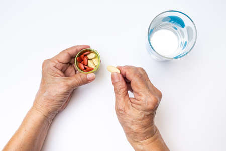 Senior woman's hands holding Vitamin C pills and Antianemia pills in bottle with polka dot glass of water, Healthcare and medical concept
