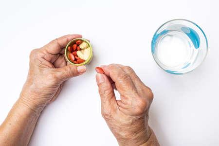 Mains d'une femme âgée cueillant des pilules antianémiques et des pilules de vitamine C en bouteille avec un verre d'eau à pois, concept de soins de santé et médical