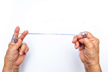 Senior womans hands pulling blue plastic rope on white background