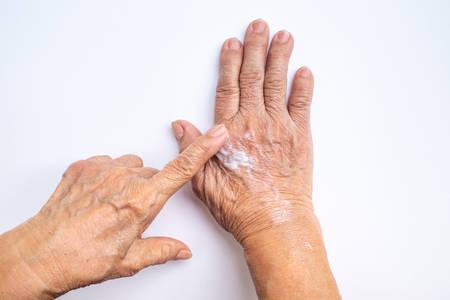 Ältere Frau, die Feuchtigkeitscreme auf ihre Hände aufträgt, die auf weißem Hintergrund lokalisiert werden, Schönheitshautkonzept Standard-Bild
