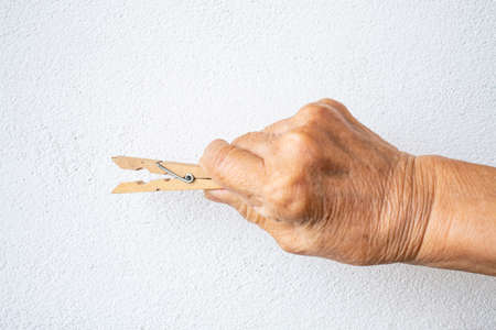 Senior woman's hand holding wooden clothes peg on white background