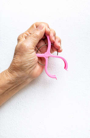 Senior woman's hand squeezing pink plastic clothes peg on white background