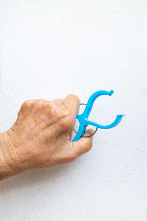 Senior woman's hand squeezing blue plastic clothes peg on white background