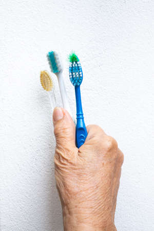 Senior womans hands holding three old toothbrushes on white background Stock Photo