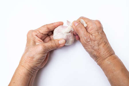 Senior woman's hand peeling Garlic or Allium sativum  isolated on white background 스톡 콘텐츠