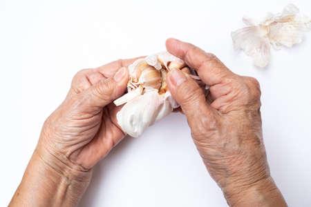 Senior woman's hand peeling Garlic or Allium sativum isolated on white background