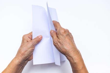 Senior woman's hand folding white paper on white background