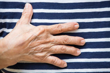 Senior womans hands action on striped T shirt background Фото со стока