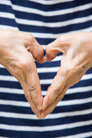 Senior womans hands  shaping of heart symbol on striped T shirt background