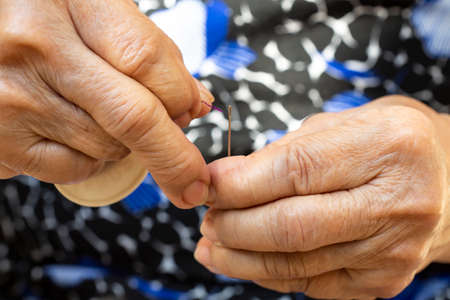 Senior womans hands trying to thread a needle, Purple colour roll of thread, Close up & Macro shot, Selective focus, Blurred and bokeh background, Tailor, Needlework concept