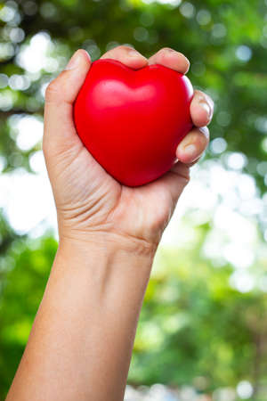 Womans left hand squeezing red stress ball on bokeh green garden background, Exercise and Massage concept