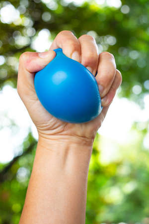 Womans left hand squeezing blue stress ball on bokeh green garden background, Exercise and Massage concept 写真素材