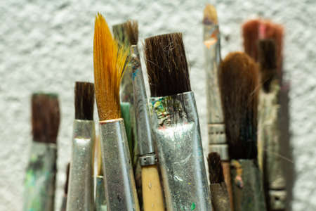 Old, Dirty Paint Brushes on white cement background, Close up & Macro shot, Selective focus, Stationery concept 스톡 콘텐츠
