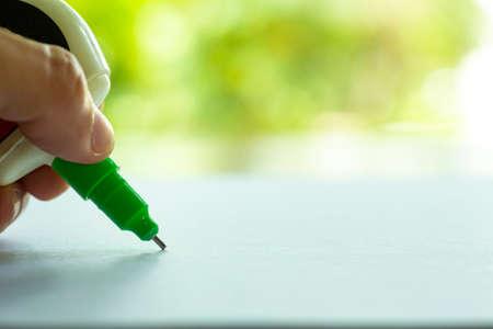 Woman's Holding Green Liquid Correction Writing Pen oder Flüssigkeit für korrekte Handschriftfehler auf weißem Papier im grünen Bokeh-Gartenhintergrund, Nahaufnahme und Makroaufnahme, selektiver Fokus, Büromaterial-Konzept