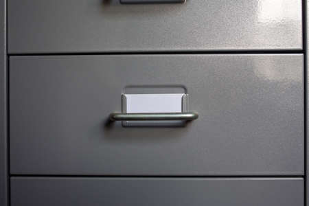 Filing cabinet with closed drawer, A white card for write letter, Grey silver metal colour, Administration and storage concept, closeup & Macro shot