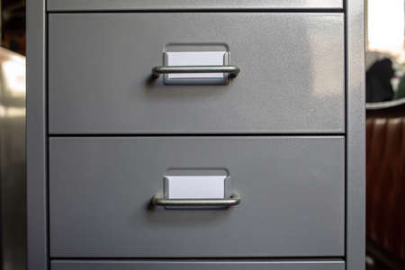 Filing cabinet with closed drawer, 2 white cards for write letter, Grey silver metal colour, Administration and storage concept, closeup & Macro shot