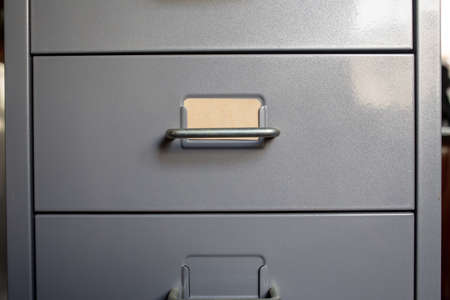 Filing cabinet with closed drawer, A brown cards for write letter, Grey silver metal colour, Administration and storage concept, closeup & Macro shot