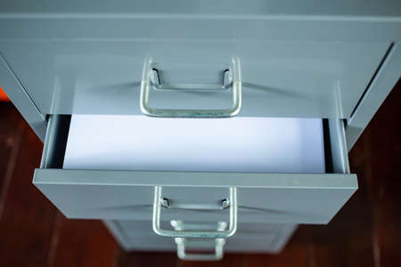 Filing cabinet with open drawer, White papers for write letter, Silver metal colour, Administration and storage concept, closeup & Macro shot, Selective focus