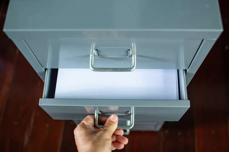 Woman's hand opening drawer of filing cabinet, Silver metal colour, White papers for write letter, Administration and storage concept, Close up shot, Selective focus