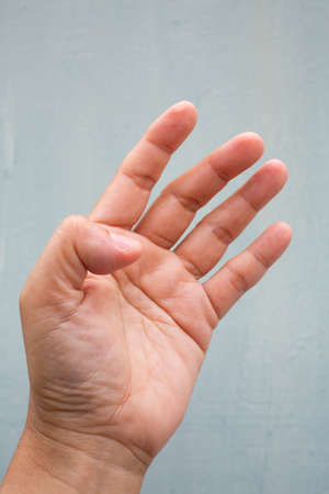 Trigger Finger lock on thumb finger of woman's side left hand, Suffering from pain, On Blue-grey colour background,  Close up & Macro shot, Office syndrome, Health care concept