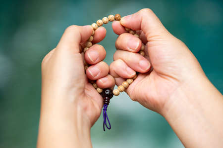 Woman's hands praying and holding a beads rosary in bokeh blue swimming pool background, Asian Body language feeling, Prayer buddhist, Religious concept