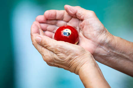 Senior woman's hands holding and praying a black and white Yin Yang religious symbol on red ball in Taoism in bokeh blue swimming pool background, Asian Body skin part, Body language feeling, Religion concept