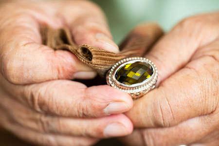 Handpolieren und Reinigen des Schmuckrings des älteren Mannes mit Cordstoff, Nahaufnahme und Makroaufnahme, selektiver Fokus, asiatischer Körperteil