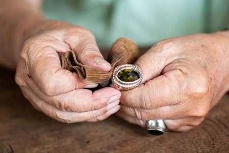 Handpolieren und Reinigen des Schmuckrings des älteren Mannes mit Cordstoff, seborrhoische Keratose-Haut der Hände, Nahaufnahme und Makroaufnahme, selektiver Fokus, asiatischer Körperteil