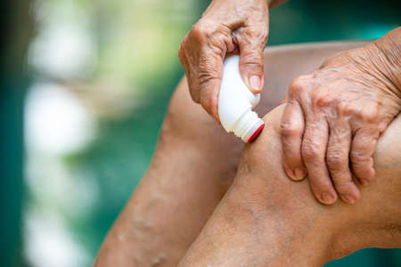 Senior woman's hands massaging her knee, Using analgesic liquid, muscle pain reliever roll on medicine, Blue swimming pool background, Close up & Macro shot, Selective focus, Asian Body skin part, About Massage, Healthcare concept Stock fotó
