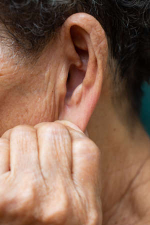 Senior woman's left hand pulling down her left ear, Grey curly hairs, Swimming pool background, Close up & Macro shot, Selective focus, Asian Body part, Healthcare concept, Symptom of hearing loss