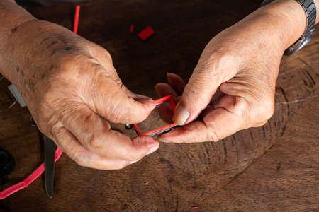Die Hände des älteren Mannes, um Amulett zu bieten, kleine Buddha-Statue mit einer Metallkappe auf Holztischtexturhintergrund, Nahaufnahme und Makroaufnahme, asiatisches Körperteil, Handwerker-Verarbeitungskonzept Standard-Bild