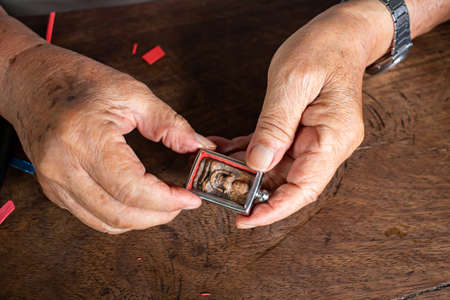 Die Hände des älteren Mannes, um Amulett zu bieten, kleine Buddha-Statue mit einer Metallkappe auf Holztischtexturhintergrund, Nahaufnahme und Makroaufnahme, asiatisches Körperteil, Handwerker-Verarbeitungskonzept