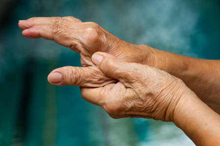 Trigger Finger, Senior woman's left hand massaging her thumb finger, Suffering from pain, Close up and macro shot, Swimming pool background, Health care concept