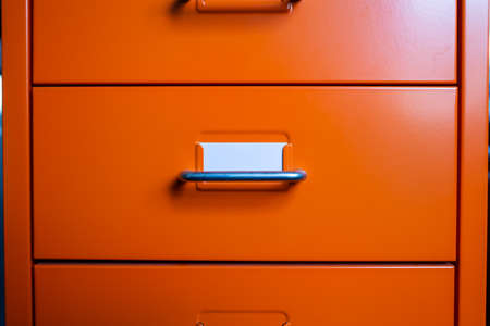 Filing cabinet with closed drawer, A white card for write letter, Orange metal colour, Administration and storage concept, closeup & Macro shot