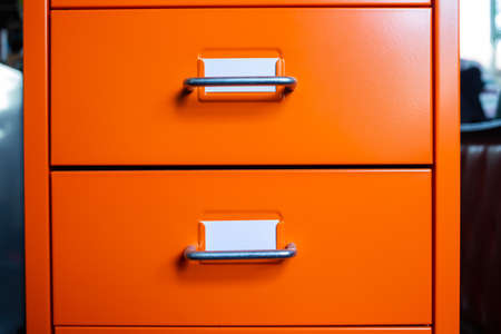 Filing cabinet with closed drawer, 2 white cards for write letter, Orange metal color, Administration and storage concept, closeup & Macro shot Stockfoto