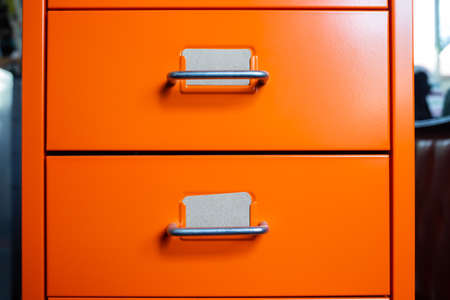 Filing cabinet with closed drawer, 2 brown cards for write letter, Orange metal colour, Administration and storage concept, closeup & Macro shot