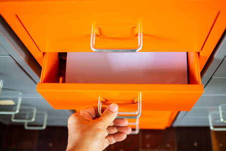 Woman's hand opening drawer of filing cabinet, Orange metal colour, White papers for write letter, Administration and storage concept, Close up shot, Selective focus